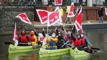 Junge ver.di-Mitglieder bei einer Tarif-Aktion in grünen Kanus auf der Alster. Sie tragen ver.di-Fahnen.